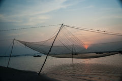 Calm scene of fishing net against purple sunset. Royalty Free Stock Images