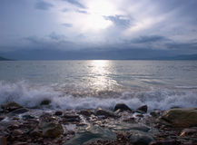 Calm Sea. Peaceful seascape at sunset showing small waves and rocks Royalty Free Stock Image