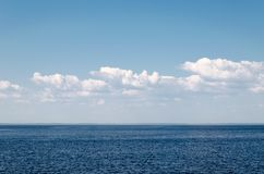 Calm sea on a background of blue sky with cloudsCalm sea against blue sky with clouds. Harmony of sea elements. Seascape. Copy royalty free stock photo