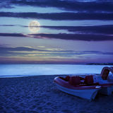 Calm sea beach with boats at night Stock Images