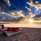 Calm sea beach with boats at sunset Stock Image