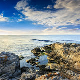 Calm sea with boulders on coast Royalty Free Stock Images
