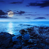 Calm sea with boulders on coast at night Stock Photo