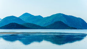 Calm sea with distant mountains and reflection in water Royalty Free Stock Photos