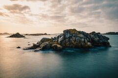 Calm sea with isles of rocks in beautiful golden dusk light after sunset