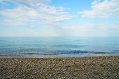 Calm sea with pebble coast Royalty Free Stock Image
