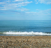 Calm sea with pebble coast Stock Image