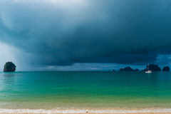 Calm sea and rain clouds in front of a tropical rain Stock Images