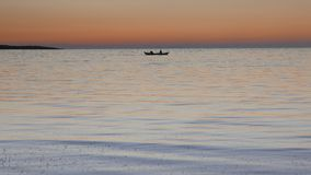 Calm sea with a rowing boat with two fishermen at. Silhouette of lone rowing boat with two fishermen under a spectacular sunset sky. 4k. Other camera movements stock video