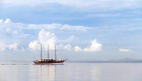 Calm sea sailing. Beautiful ship sailing on a calm sea with a nice cloudscape Stock Image