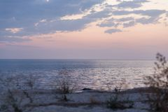Calm  sea shore in rays of sunset sky.  Pink color of the sky. Silence, relaxation.  Stock Photos