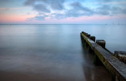Calm sea at sunset. A view of the calm ocean and a wooden groyne, at sunset Stock Images