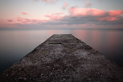 Calm sea sunset. With a jetty Royalty Free Stock Images