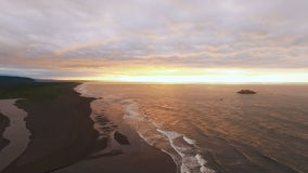 Calm sea at sunset. Mountain stream flows into the ocean. The orange sun is shining at the camera stock video footage