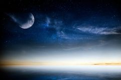 Calm sea sunset over night sky with stars and moon royalty free stock images