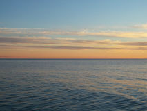 Sunset clouds over the sea. Calm sea and sunset sky stock photo