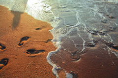 Calm sea surf and footsteps at sunset Stock Photos