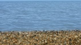 Calm sea surface on background sandy and rocky shore. Beautiful sea landscape. Calm sea surface on background sandy and rocky shore. Close up tranquil waves on stock video footage