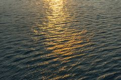 Sunset water background texture. Calm sea water with waves during sunset stock photography