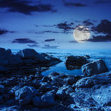Calm sea wave on rocky shore at night Royalty Free Stock Photos