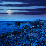 Calm sea wave on rocky shore at night Stock Photo