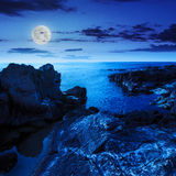 Calm sea wave touches boulders at night Royalty Free Stock Photo