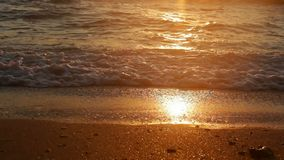 Calm sea waves breaking on the shore at sunset. Closeup stock video footage