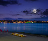 Calm sea waves on city beach at night. Calm sea wave on city beach with clubs, boats and umbrella at night in  full moon light Royalty Free Stock Photo