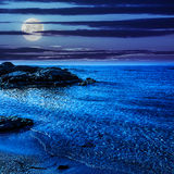 Calm sea with waves on  sandy beach at night. Calm sea with some wave on  sandy beach with stones at night Stock Images