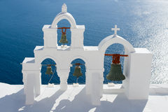 Calm sea, white church arch, bells Santorini. View on calm sea surface through traditional Greek white church arch with cross and bells in village Oia of Stock Photo
