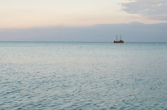 Calm sea and a wooden boat on the horizon Stock Photos