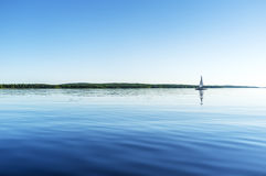 Calm sea. Yacht catamaran with a sail in calm water, the view from the height of the water surface royalty free stock photo