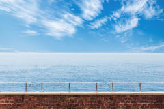 Calm seascape view. Calm sea and cloudy sky view with brick wall and railing in the foreground Royalty Free Stock Image