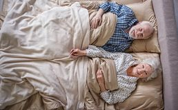 Calm senior couple waking up in the morning. Top view of happy elderly husband and wife lying in bed. They are looking at camera with smile. Concept of peace Royalty Free Stock Photo
