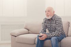 Calm senior man watching tv copy space. Calm senior man watching tv, sitting on couch with remote controller, copy space Royalty Free Stock Photo