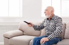 Calm senior man watching tv copy space. Calm senior man watching tv, sitting on couch with remote controller, copy space Royalty Free Stock Photos