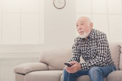 Calm senior man watching tv copy space. Calm senior man watching tv, sitting on couch with remote controller, copy space Stock Photos