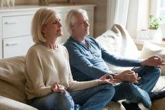 Senior couple meditating practicing yoga together sitting at hom. Calm senior middle aged couple practicing yoga together sitting in lotus pose on sofa, mindful stock photos