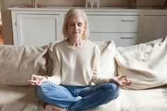 Calm senior woman practicing yoga meditating on couch. Calm senior woman relax on couch meditating in lotus position, peaceful aged female practice yoga at home stock photos
