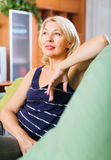 Calm senior woman relaxing in couch. Portrait of calm senior woman relaxing in couch at home Stock Image