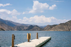 Calm serene dock at a blue lake surrounded by mountains Stock Images