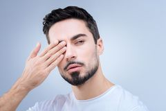 Calm serious man doing exercises while improving his eyesight Royalty Free Stock Image