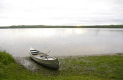 Calm Shore and Canoe at Dusk. A canoe sitting on the shore waiting for an evening paddle Royalty Free Stock Photos