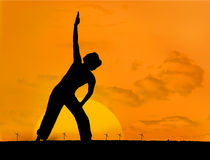 Calm silhouette of woman practicing yoga Stock Image