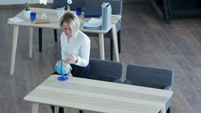 Calm single young woman relaxing at work, looking at globe dreaming about holidays. Professional shot in 4K resolution. 091. You can use it e.g. in your stock footage