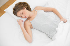 Calm slender woman lying sleeping on her bed under the cover Royalty Free Stock Photos