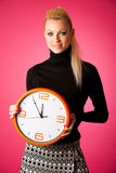 Calm smiling woman with big orange clock gesturing no rush, enou Royalty Free Stock Photography