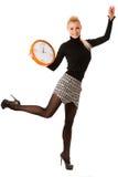 Calm smiling woman with big orange clock gesturing no rush, enou Stock Photo
