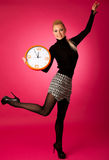 Calm smiling woman with big orange clock gesturing no rush, enough time to be punctual. stock images