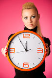Calm smiling woman with big orange clock gesturing no rush, enough time to be punctual. royalty free stock image